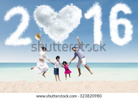 Joyful asian family celebrating new year on the beach, jumping together under cloud shaped numbers 2016 - stock photo