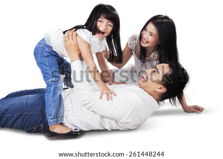 Joyful asian family laughing and playing together on the floor, shot in the studio isolated on white - stock photo