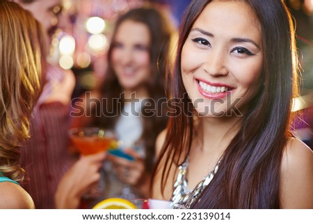 Joyful Asian girl at a party, her friends in the background  - stock photo