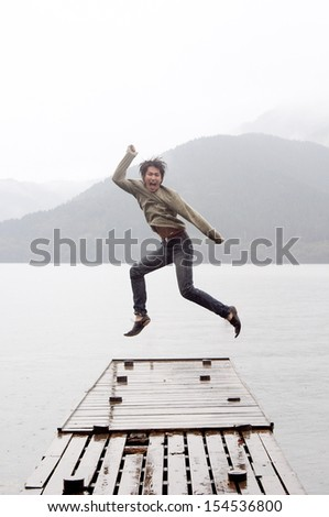 Joyful asian japanese young man jumping on a wooden pier while visiting a dreamy lake landscape with mountains during a cloudy and rainy day, outdoors.
