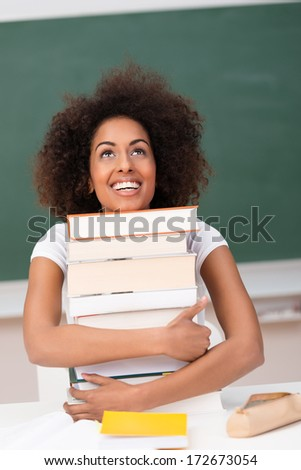 Joyful attractive young African American student hugging her text books as she realizes her dream to attend university - stock photo