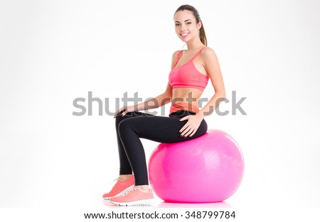 Joyful attractive young sportswoman in tracksuit sitting on pink fitball isolated over white background - stock photo