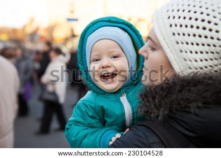 Joyful baby boy and his mother outdoors in wintertime, with blurred people in background - stock photo