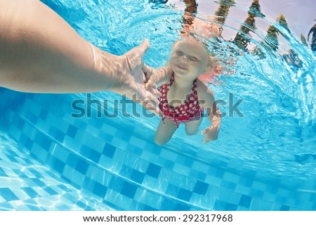 Joyful baby girl diving underwater with fun and holding parents hand for assistance in swimming pool. Healthy active family lifestyle, children water sport activity with mother on summer vacation - stock photo
