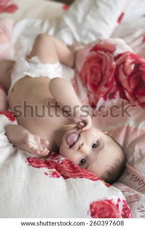 joyful baby lying in bed on his back and showing tongue - stock photo