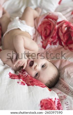 joyful baby lying on his back - stock photo