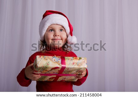 Joyful baby with Christmas gift in Santa's hat. Getting ready to decorate a Christmas tree. Christmas, New Year - stock photo