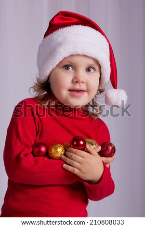 Joyful baby with Christmas toys in Santa's hat. Getting ready to decorate a Christmas tree. Christmas, New Year