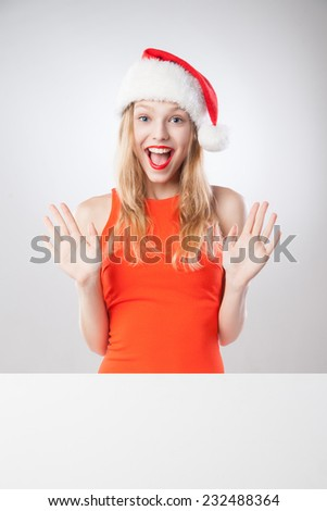 Joyful Beautiful christmas woman in santa hat holding empty board isolated on white background - stock photo