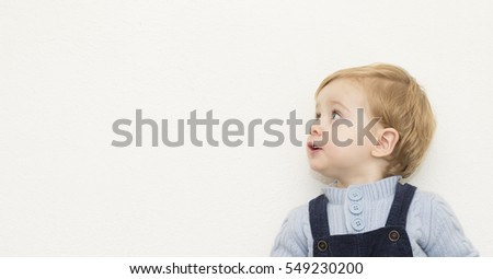 Joyful beautiful little boy looking at copyspace over white background