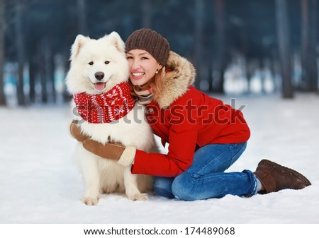 Joyful beautiful stylishly dressed young woman in red jacket hugging white Samoyed dog outdoors in winter day