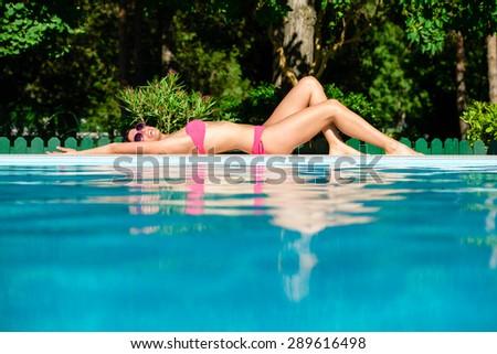 Joyful beautiful woman in bikini sunbathing at poolside on summer vacation. Relax and joy on summertime. - stock photo