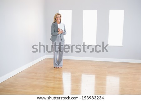 Joyful blonde realtor standing in an empty room holding documents