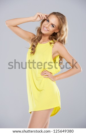 Joyful blonde woman with a beautiful smile posing in a trendy yellow miniskirt, three quarter studio portrait - stock photo