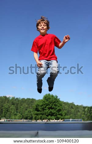 Joyful boy dressed in red T-shirt jumps on trampoline at sunny summer day - stock photo