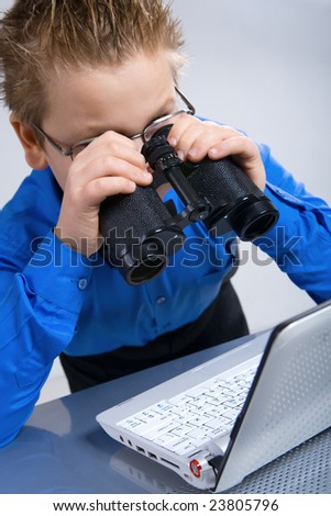 Joyful boy looking at computer screen in binoculars