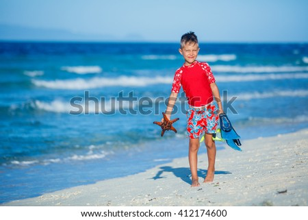 Joyful boy on the tropical beach with equipment to scuba diving and starfish. - stock photo