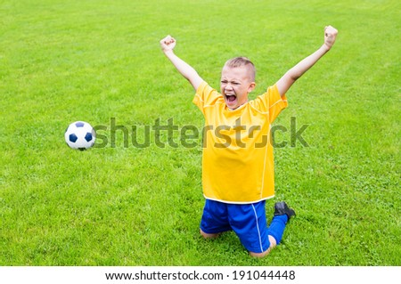 Joyful boy soccer player after goal scored. Natural grass.