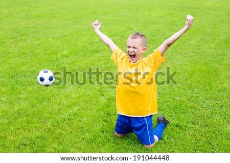 Joyful boy soccer player after goal scored. Natural grass. - stock photo
