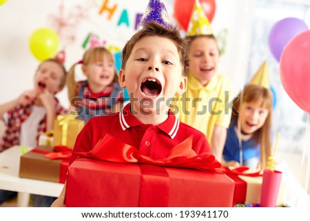 Joyful boy with big red giftbox looking at camera with his friends on background - stock photo