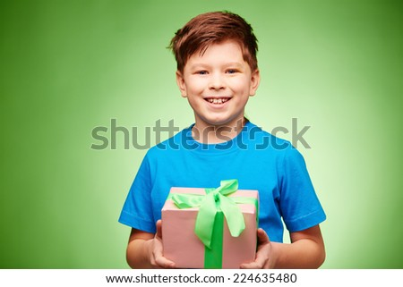 Joyful boy with giftbox looking at camera over green background - stock photo