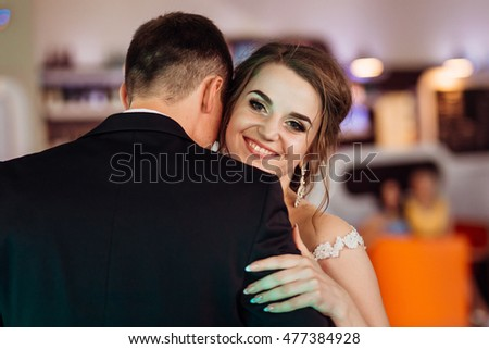 Joyful bride looks over groom's shoulder while dancing in the restaurant