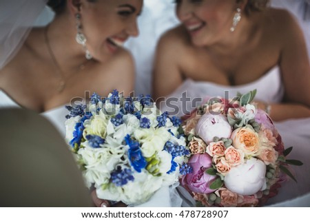 Joyful brides with the bouquets of flowers