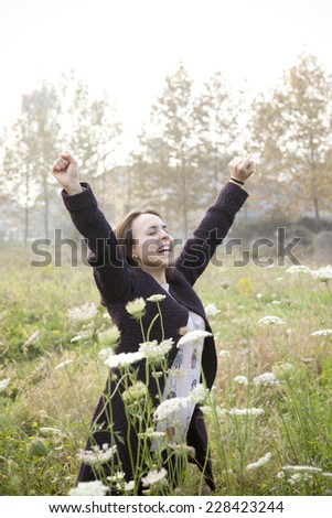 joyful brunette girl with coat with her arms raised in a wildflowers field  in the countryside with soft sunlight - stock photo