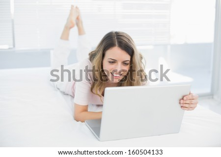 Joyful brunette woman making use of her notebook lying on her bed