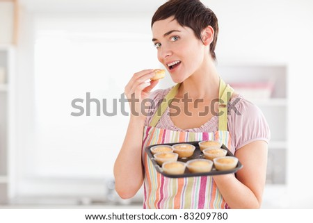 Joyful brunette woman showing muffins while eating one in a kitchen - stock photo