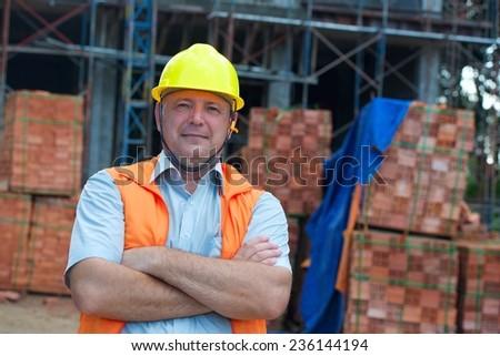 Joyful builder in helmet on a building site - stock photo