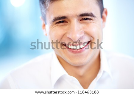 Joyful businessman looking at camera with smile - stock photo