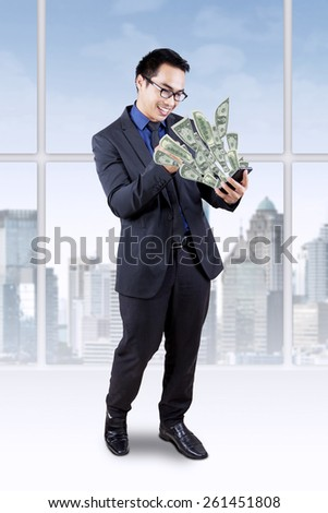 Joyful businessman standing in the office while looking at money dollar coming out from his cellphone - stock photo