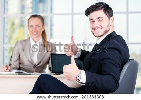 Joyful businessmen. Two businessman sitting at the table until one man businessman looking at the camera and showing thumb up. - stock photo