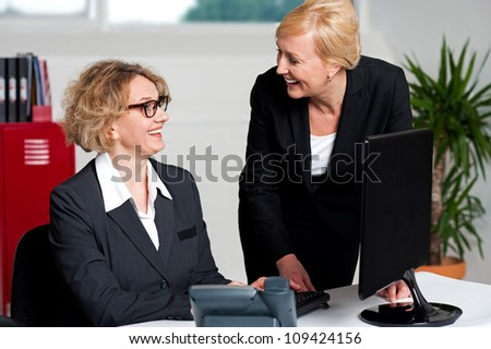 Joyful businesswomen enjoying at work desk during office hours