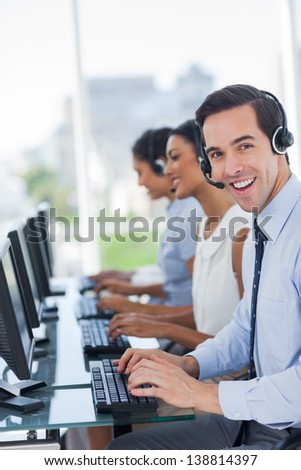 Joyful call centre agent working with his headset