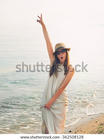 Joyful casual girl walking on a sea beach and happy screaming with hand up