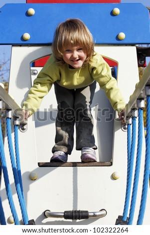 joyful child playing on colorful playground - stock photo