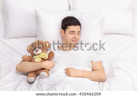 Joyful childish guy sleeping peacefully with a teddy bear on a comfortable bed - stock photo