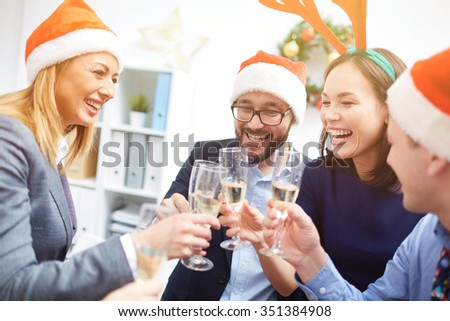 Joyful colleagues toasting with champagne at corporate Christmas party