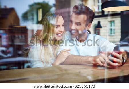 Joyful couple at coffee shop browsing photos on smartphone - stock photo
