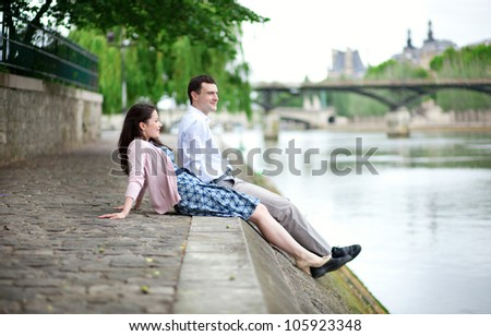 Joyful couple is sitting on the embankment - stock photo