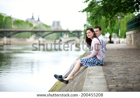 Joyful couple is sitting on the embankment in Paris - stock photo