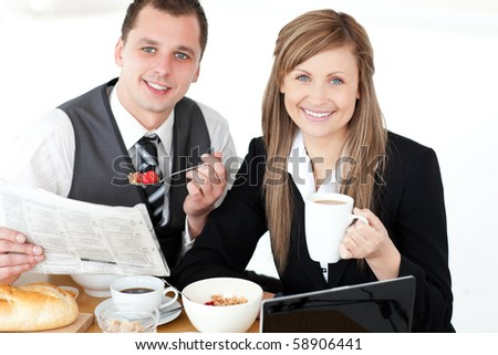 Joyful couple of businesspeople having breakfast smiling at the camera against white background