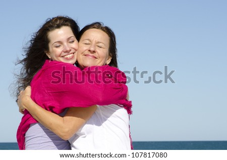 Joyful cuddle of mother and daughter with happy smile, clear blue sky as background and copy space. - stock photo