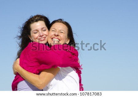 Joyful cuddle of mother and daughter with happy smile, clear blue sky as background and copy space.