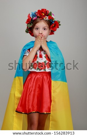 Joyful cute little girl in the Ukrainian national costume holding a big flag of Ukraine on a gray background