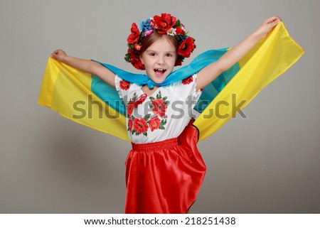 Joyful cute little girl in the Ukrainian national costume holding a big flag of Ukraine on a gray background - stock photo