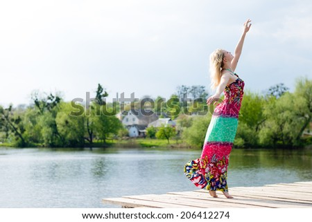 joyful dancing: posing beautiful blond young slim woman enjoying stretching in long light dress at water lake on summer green outdoors & blue sky copy space background portrait image - stock photo