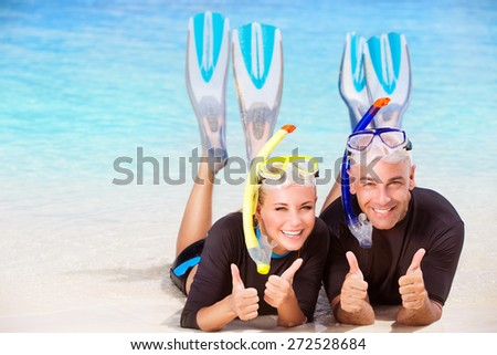Joyful diver couple lying down on the beach, wearing mask and flippers for snorkeling, gesturing by hands good mood, active summer time vacation